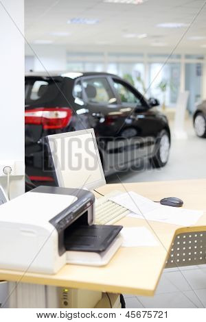 Computer, printer and documents on wooden desk and new car stands in office of car shop. Shallow depth of field. Focus on display.