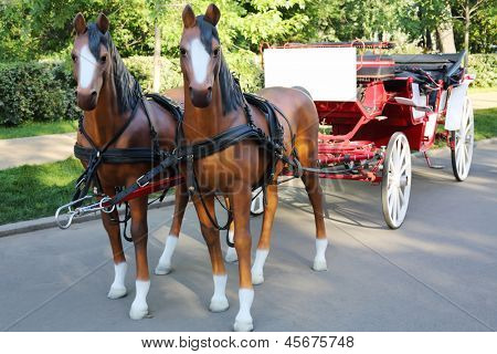 Two artificial sledge of horses harnessed wagon in park at summer day.