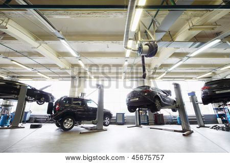 Back of four black cars in garage with special equipment for repair.