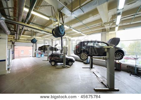 Cars on lifts in small service station. Cars prepared to diagnosis and repair.
