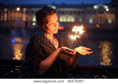 A girl in a black dress shows a fire show.