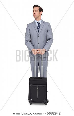 Serious businessman waiting with his luggage on white background