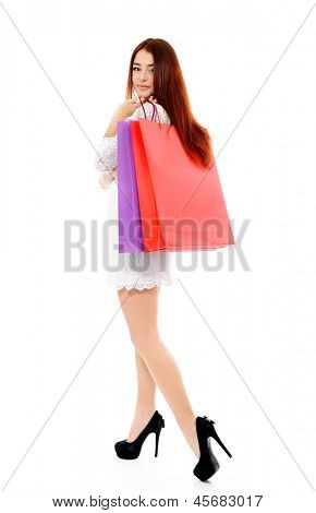 shopaholic, shopping girl, young woman on high heels with colored shopping bags, full length portrait over white