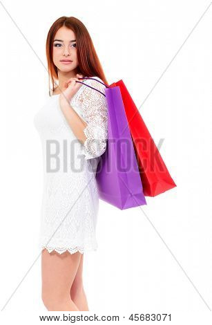 shopaholic, shopping girl, young woman on high heels with colored shopping bags, over white