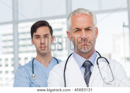 Two serious doctors standing in front of the camera