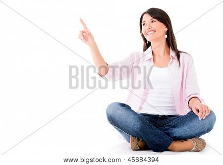 Woman sitting on the floor and pointing with her finger - isolated