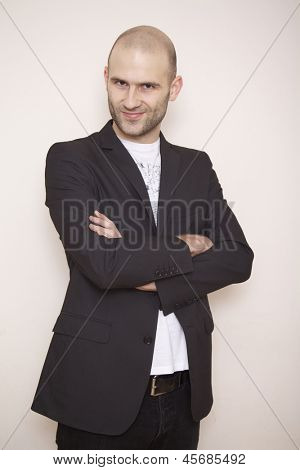 fashion shot of an elegant young man wearing suit on grey background