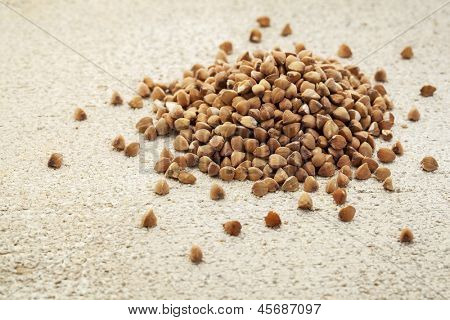 a roasted buckwheat grain  (kasha) on a rough white painted barn wood background