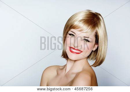 portrait of a beautiful woman in short blond bob with bright make-up on studio background