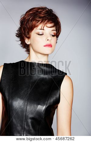 portrait of a young woman in leather dress with red hair wearing short pixie crop hairstyle on studio background