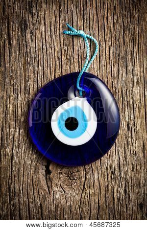 glass turkish eye on wooden background
