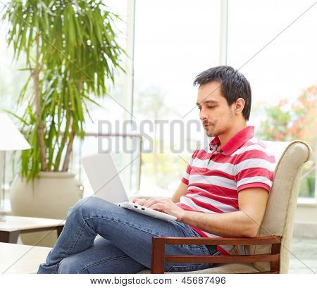 Handsome young man sits at bright hotel or coffee shop interior and working on laptop computer.