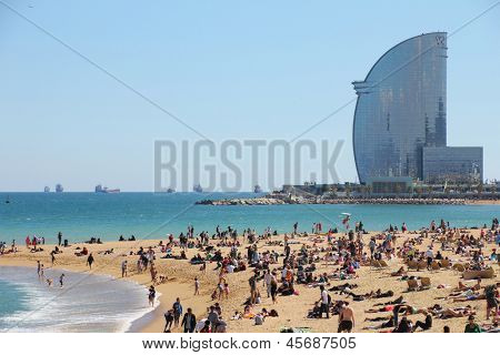 BARCELONA - MAY 3: city beach,  400 meters long, it one of 10 best urban beaches of the world. Tourists rest along Barceloneta beach, May 03, 2013 in Barcelona, Spain