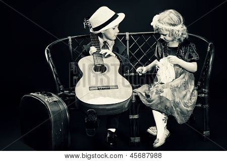 Cute little boy is playing the guitar to the charming little lady. Retro style.