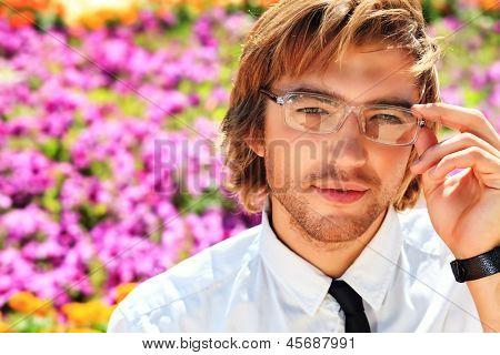 Portrait of a young business man over summer background.