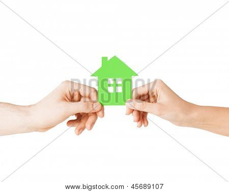closeup picture of woman and man hands holding green house