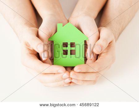 Closeup imagen de mujer y hombre manos sosteniendo la casa verde