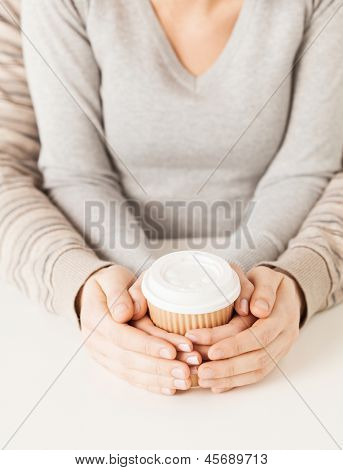 woman and man hands holding take away coffee cup