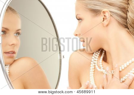 woman with pearl necklace looking in the mirror