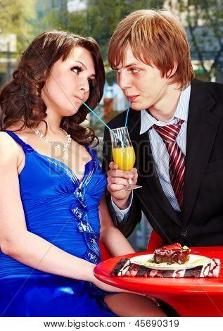 Loving couple eating cake in restaurant.