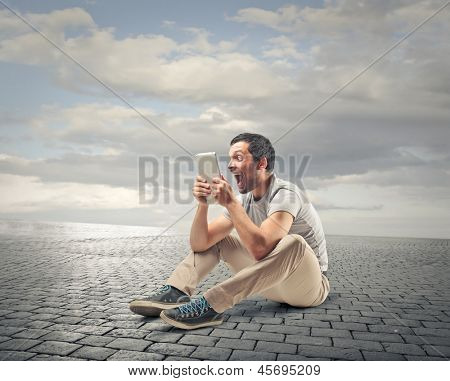 young man sitting on the floor looks with stupor the tablet