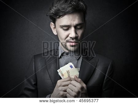 dishonest man puts money in the jacket