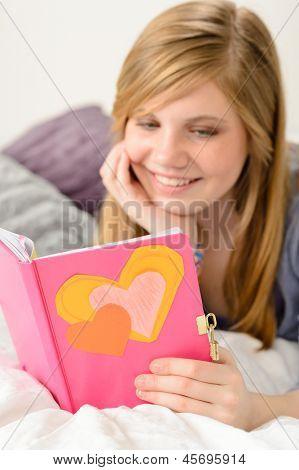 Garota jovem amigável, lendo seu diário de memórias