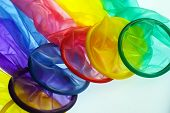 foto of condom  - set of condoms of different colors on a white surface - JPG