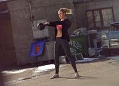 stock photo of swing  - Young fitness woman swinging the kettlebell during crossfit training - JPG