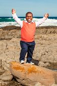 stock photo of midget  - dwarfish african man throwing his hands up laughing openly with a rocky beach in the background - JPG