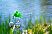 picture of sounding-rod  - Fishing bite alarm bell in readinesson blurred green vegetation and river - JPG