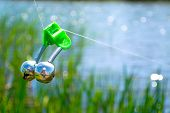 foto of sounding-rod  - Fishing bite alarm bell in readinesson blurred green vegetation and river - JPG