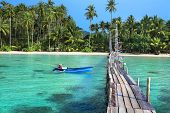 stock photo of pacific islands  - landscape of tropical island beach with beautiful wooden jetty and motorboat in front of coast with white sand and a plenty of palm trees - JPG