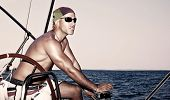 stock photo of work crew  - Handsome strong man working on sail boat - JPG