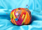 Colorful buttons and multicolor wool ball on color fabric background