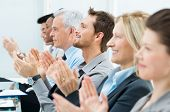 stock photo of applause  - Businesspeople In A Row Greets With Clapping Hands - JPG