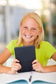 stock photo of pre-adolescent girl  - happy teen girl holding tablet computer at home - JPG