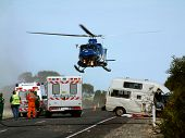 image of campervan  - a helicopter lifts off, with patient on board at road crash scene