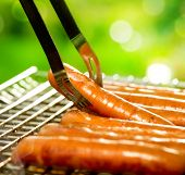 Grilled Sausage on the flaming Grill. BBQ. Bearbeque outdoors. Barbecue