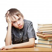 stock photo of schoolboys  - Portrait of upset schoolboy sitting at desk with books holding his head - JPG