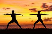 stock photo of serenity  - Yoga people training and meditating in warrior pose outside by beach at sunrise or sunset - JPG
