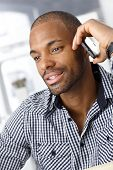 Closeup portrait of handsome Afro-American man on mobile phone call.