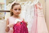 Beautiful girl tries on a bright red dress in the store childrens clothes