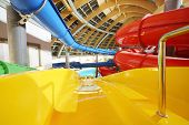 Big multi-colored indoor water slides in aquapark. Descent yellow slide.
