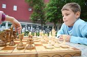 Boy looks like hand of girl moves chess piece on chessboard in park.