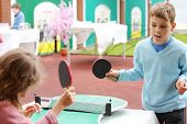 Little girl and boy in blue play table tennis in park at summer day. Focus on boy.