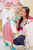 Smiling little girl and her mother cheek to cheek in clothing store, hangers with clothes in their h