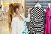 Little girl takes hanger with striped gown from stand in clothing store