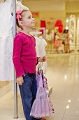 Little girl stands leaning on rack and holds hangers with light-violet skirt and flower-patterned bl