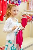 Little girl stands  holding hanger with closed swimsuit and turning something in mind